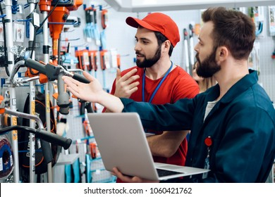 Two salesmen in red shirt and baseball cap and blue robe are checking tooks inventory with laptop in power tools store.