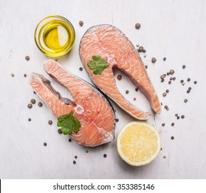 Two salmon steak, butter, pepper and salt, lemon, herbs on wooden rustic background top view close up