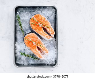 Two salmon steaks with thyme in a pan with ice.Red fish.