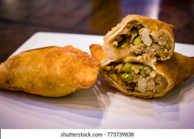 Two Samosas with One of the Samosas Cut in Half Showing the Potato and Peas Stuffing