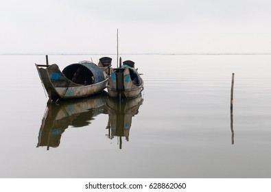 Two sampan shrimp fishing boats with a reflection in a lake between Hue and Hoi An in Central Vietnam.