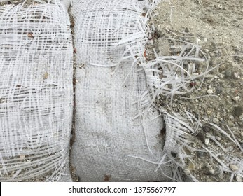 Two sandbags pressed together, one has a large tear and wild threads.