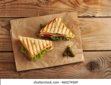 two sandwich pickles on a paper towel on wooden background in rustic style. the view from the top