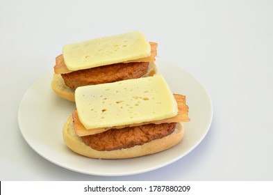 two sandwiches with beef, bacon and cheese on white plate, closeup, isolated on white background