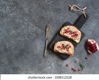 Two sandwiches with chicken pate and pomegranate seeds on a black board on grey background. Top view