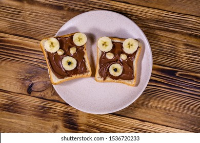Two sandwiches with chocolate spread on plate. Sandwich like a bear muzzle. Top view