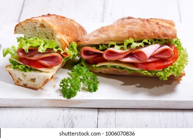 two sandwiches with ham and vegetables on wooden board