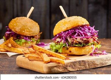 Two sandwiches with pulled pork, french fries and glass of beer on wooden background