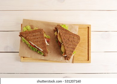 two sandwiches from triangular pieces of bread with chicken breast, cheese and greens on paper on white wooden background - top view