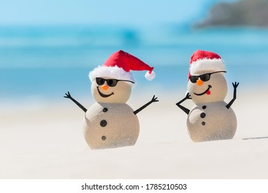 Two Sandy Christmas Snowmen are wearing sunnies and celebrating Christmas on a beautiful beach