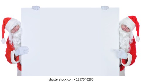 Two Santa Claus on either side of a wide blank poster. Both men are holding on to the paper and one is pointing at the blank space.