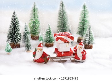 Two Santa Clauses are coming with presents on sledge along snowy forest road