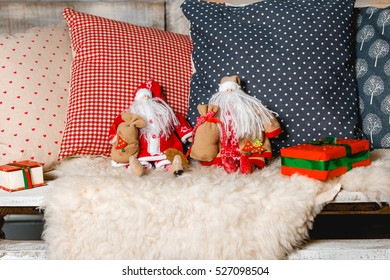 Two santa dolls sitting at colorful pillows. Christmas concept.