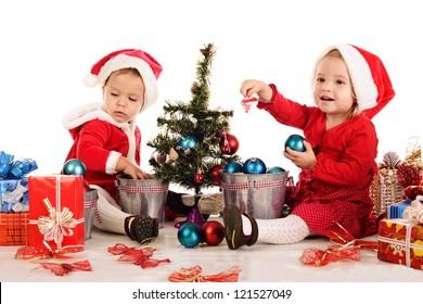 two santas girls decorating new year tree