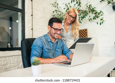 Two satisfied casual business people working in bright office.