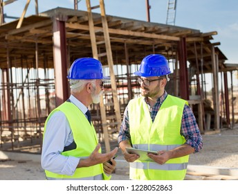 Two satisfied engineers with tablet talking at building site