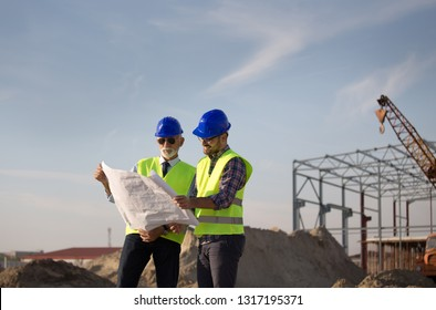 Two satisfied engineers talking at building site with metal construction in background