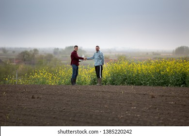 Two satisfied farmers with laptop shaking hands in yellow rapeseed field
