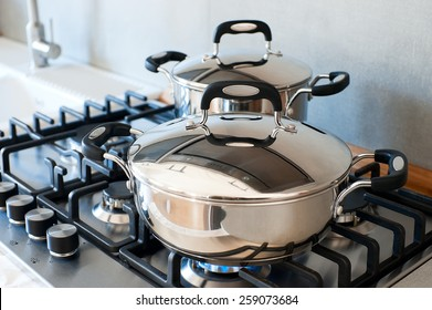 Two saucepans stainless steel on gas stove