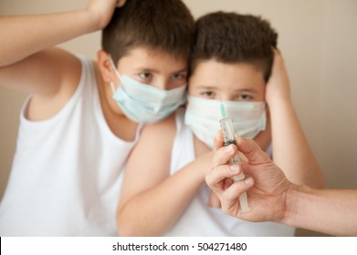 two scared boys in a medical mask looking at hand with syringe