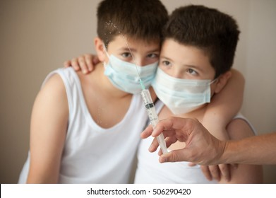 two scared boys in medical mask looking at hand with syringe