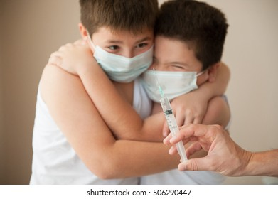 two scared children in medical mask looking at hand with syringe