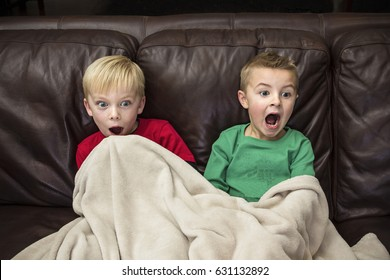 Two scared little boys sitting on the couch watching television together. The young boys are shocked and show a fearful expression as they view the violent entertainment content on the screen