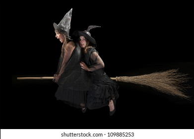 two scared witches flying on a broom. Black background
