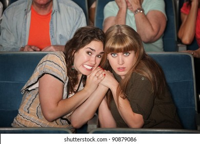 Two scared women huddle close in a theater