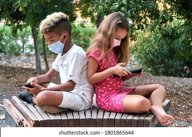 Two school age 9s 10s multi racial kids wear face mask sit together on bench back to back use cellphone and tablet devices ignore each other. Phubbing, new generation addicted with modern tech concept