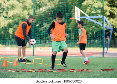 Two school boys are running ladder drills on the turf during football summer camp. Intense soccer training with coach.