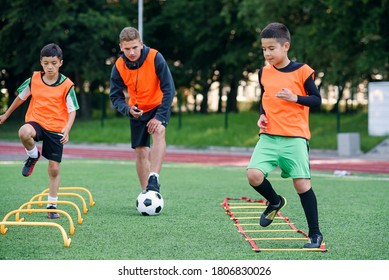 Zwei Schuljungen laufen im Sommerlager des Fußballs auf dem Rasen Leiter-Drills. Intensives Fußballtraining mit Trainer.