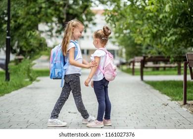 Two school friends met near the school. The concept of school, study, education, friendship, childhood