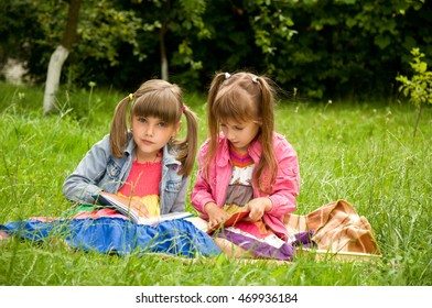 Two school girls are preparing a lesson in nature. They read book
