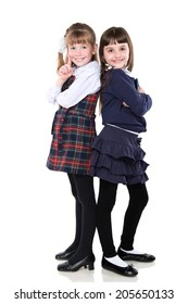 Two school girls stood back to back on white