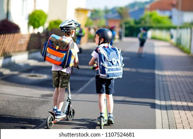 Two school kid boys in safety helmet riding with scooter in the city with backpack on sunny day. Happy children in colorful clothes biking on way to school. Safe way for kids outdoors to school.