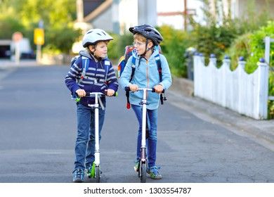 Two school kid boys in safety helmet riding with scooter in the city with backpack on sunny day. Happy children in colorful clothes biking on way to school.