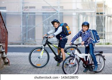 Dos escolares con casco seguro montando en bicicleta en la ciudad con mochilas. Niños felices con ropa colorida yendo en bicicleta de camino a la escuela. Una forma segura para los niños al aire libre
