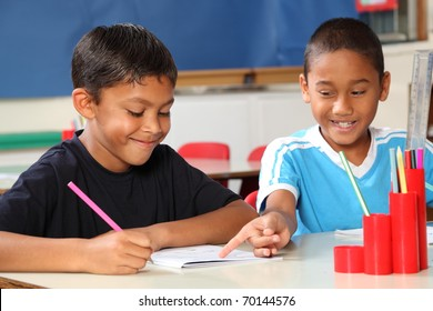 Two schoolboys helping each other learn in class during lessons