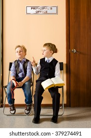 Two schoolboys are sitting next to principal's office. They are twin, but they have different each other behavior and clothes. For creating this picture were used two image of one and the same boy.