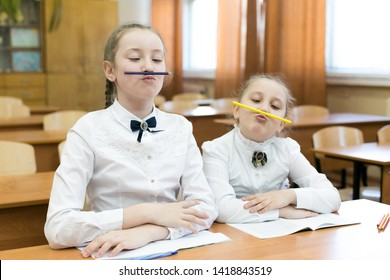 Two schoolgirls pinch a pencil with their lips to the nose, make a funny facial expression. Children indulge in school in the classroom make face mimicry.