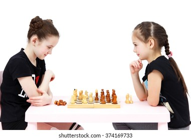 Two schoolgirls play chess on white background