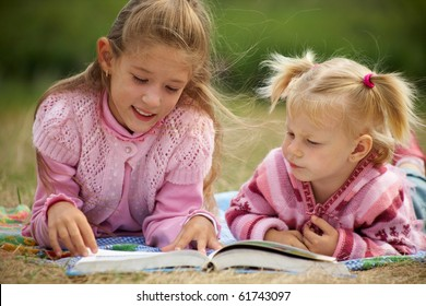 two schoolgirls is  reading  a big  book on the background of green meadows