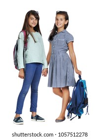 Two schoolgirls with school bags against white background