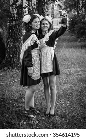 Two schoolgirls in school uniform graduates make a picture for memory. Black and white photography.