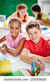 Two schoolkids looking at camera while drawing on background of little girls