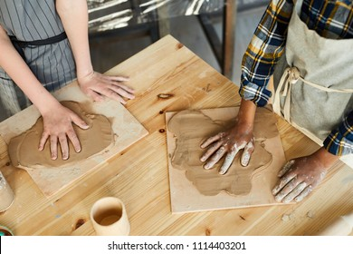 Two schoolkids making handprints on rolled pieces of clay on wooden boards at handcraft lesson