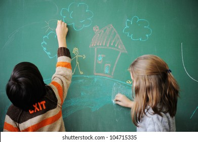 Two schoolkids wriing on blackboard
