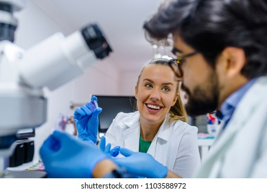 Two scientists conducting research in a lab environment. Scientists Team Working In Laboratory Doing Research, Man And Woman Making Scientific Experiments Doctors In Lab
