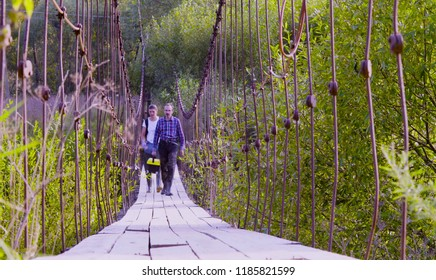 Two scientists ecologists walking on hanging bridge over a forest river. Field work.